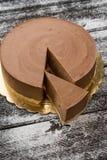 褐巧克力色乳酪蛋糕和切片在木 免版税图库摄影