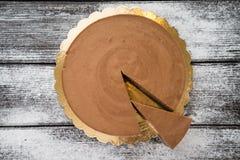 褐巧克力色乳酪蛋糕和切片在木 免版税库存照片