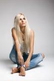 褴褛牛仔裤和背心的白肤金发的妇女 免版税图库摄影
