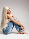 褴褛牛仔裤和背心的白肤金发的妇女 库存照片