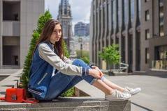 褴褛牛仔裤的女孩坐街道 免版税库存照片