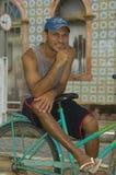 巴西人坐他的在他的房子前面的自行车 免版税库存照片