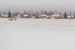 西伯利亚村庄在冬天 背景 免版税库存照片
