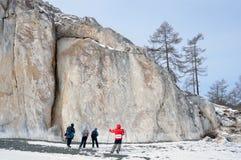 西伯利亚,伊尔库次克地区,海角萨根扎巴,俄罗斯, 2017年3月, 10日 走在贝加尔湖海岸的游人  大横向山山 免版税库存照片