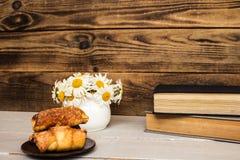 戴西和书新月形面包花束在木头 库存图片