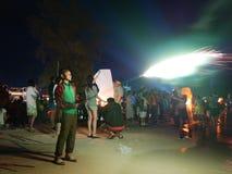 西哈努克12月31日2016年海滩柬埔寨,拿着在海滩社论的亚洲少年男性爆炸的烟花 免版税库存图片