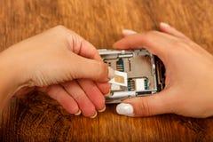 西姆卡片的插入在智能手机的 免版税库存照片