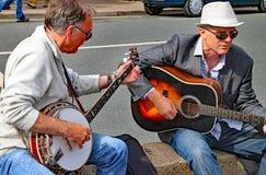 西德茅斯,德文郡,英国- 2012年8月8日:两个人弹一把吉他和一架班卓琵琶在即兴街道表现在广场 免版税库存图片