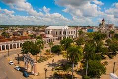 西恩富戈斯,古巴:古巴城市的看法在公园何塞马蒂广场顶部的有与大教堂的一个凯旋门的洁净 库存照片