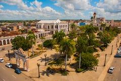 西恩富戈斯,古巴:古巴城市的看法在公园ose马蒂广场顶部的有与大教堂的一个凯旋门的洁净 免版税库存图片