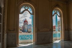 西恩富戈斯,古巴:看法通过宫殿的Windows城市和大厦自治市的中心的 免版税库存照片