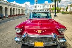 西恩富戈斯,古巴- 2012年3月22日:在地道街道古巴西恩富戈斯上的红色老减速火箭的汽车 免版税库存图片