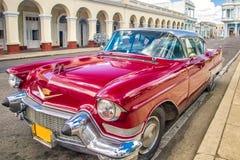 西恩富戈斯,古巴- 2012年3月22日:在地道街道古巴西恩富戈斯上的红色老减速火箭的汽车 免版税库存照片