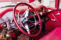 西恩富戈斯,古巴- 2018 3月11日,红色fitfyfive的薛佛列350 - 1955年雪佛兰游牧人Restomod 仪表板的看法与指点whe的 库存照片