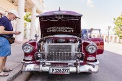 西恩富戈斯,古巴- 2018 3月11日,红色fitfyfive的薛佛列350 - 1955年雪佛兰游牧人Restomod 在前面帽子下的看法在engi 免版税图库摄影