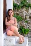 西班牙十几岁的女孩坐与岩石墙壁的一个老门  免版税库存照片