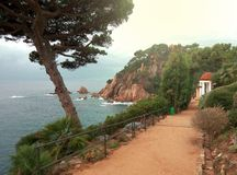 西班牙和美好的鲜绿色颜色海岩石海岸  导致一间美丽的白色凹室的道路 图库摄影
