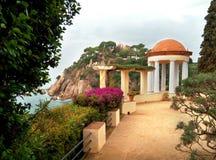 西班牙和美好的鲜绿色颜色海岩石海岸  导致一间美丽的白色凹室的道路 免版税图库摄影