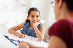 西班牙在家做学校家庭作业的母亲帮助的女孩 库存照片