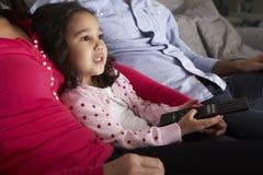 西班牙女孩坐沙发和观看的电视与父母 库存照片