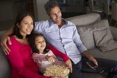 西班牙女孩坐沙发和观看的电视与父母 图库摄影
