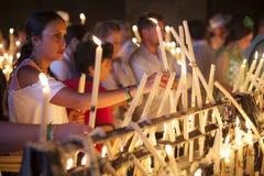 西班牙妇女在教会里打开蜡烛 免版税库存图片