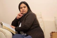 西班牙妇女在长沙发读圣经 免版税库存照片