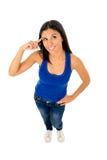 西班牙妇女微笑愉快在指向她顶头认为的上面和牛仔裤 免版税库存照片