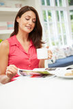 西班牙妇女读书杂志在厨房里 库存照片
