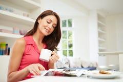 西班牙妇女读书杂志在厨房里 免版税库存照片