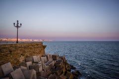 西班牙安大路西亚卡迪士木板走道日落街灯日落海滩 免版税库存照片