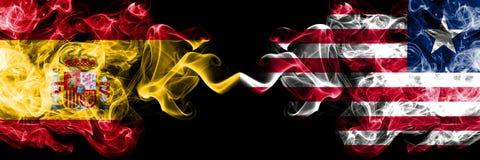 西班牙对利比里亚,肩并肩被安置的利比里亚发烟性神秘的旗子 厚实色柔滑抽西班牙语和利比里亚的旗子, 库存照片