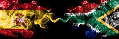西班牙对南非,肩并肩被安置的非洲发烟性神秘的旗子 厚实色柔滑抽西班牙语和南非的旗子 图库摄影