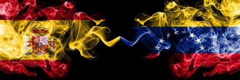 西班牙对委内瑞拉,肩并肩被安置的委内瑞拉发烟性神秘的旗子 厚实色柔滑抽西班牙语和委内瑞拉的旗子, 库存照片
