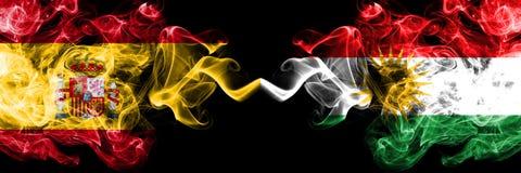西班牙对库尔德斯坦,肩并肩被安置的库尔德发烟性神秘的旗子 厚实色柔滑抽西班牙语和库尔德斯坦的旗子, 库存照片