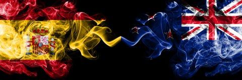 西班牙对新西兰,肩并肩被安置的新西兰的发烟性神秘的旗子 厚实色柔滑抽旗子西班牙语和新 库存图片