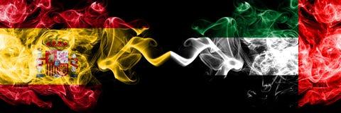 西班牙对阿拉伯联合酋长国,肩并肩被安置的Emirati发烟性神秘的旗子 厚实色柔滑抽旗子西班牙语和 免版税库存图片