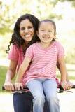 年轻西班牙循环在公园的母亲和女儿 免版税库存图片