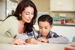 西班牙有家庭作业的母亲帮助的儿子在表上 免版税库存图片