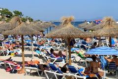 西班牙海滩的日光浴者在夏天 免版税库存照片