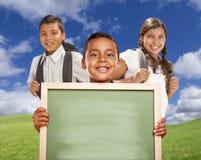 西班牙男孩和女孩拿着空白的粉笔板的领域的 库存照片