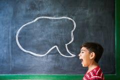 西班牙男孩尖叫在有云彩的教室在黑板 免版税库存图片