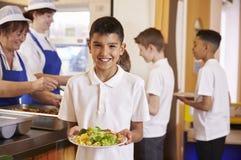 西班牙男小学生在学校食堂拿着食物板材  库存照片