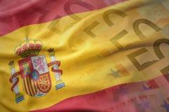 西班牙的五颜六色的挥动的国旗欧元金钱钞票背景的 库存照片