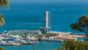 从西班牙的明信片 口岸在巴塞罗那-太阳闪闪发光在一个风帆被塑造的大厦的玻璃在一个人做了海岛 库存照片