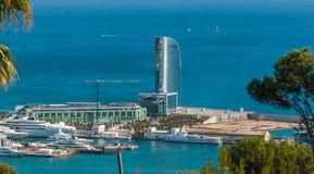 从西班牙的明信片 巴塞罗那港-晒黑闪闪发光在一个风帆被塑造的大厦的玻璃在一个人造海岛上 库存图片