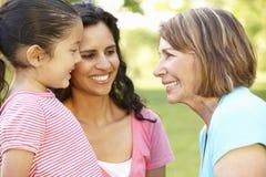 西班牙祖母、放松在公园的母亲和女儿 库存照片
