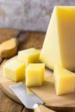 西班牙语楔子治疗了坚硬山羊母牛和在木盛肉盘的立方体切的母羊乳酪 在表的刀子和叉子 传统的开胃菜 图库摄影