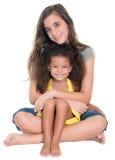 西班牙青少年的拥抱一个小非裔美国人的女孩 免版税库存图片