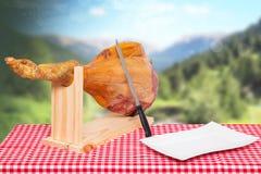 西班牙食物 西班牙塞拉诺火腿和在一红色方格的一块空的白色板材的一条前面腿的特写镜头在一个木立场的 免版税库存照片